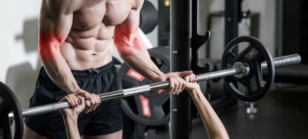 personal trainer with barbell flexing muscles in gym