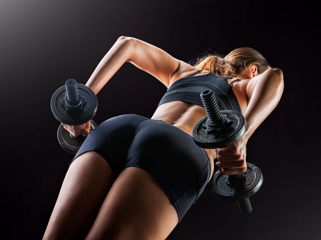 crossfit woman doing squats with dumbbells