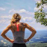 fitness woman standing near tree looking below