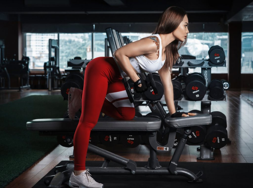 woman doing dumbbell row exercise and using weight bench