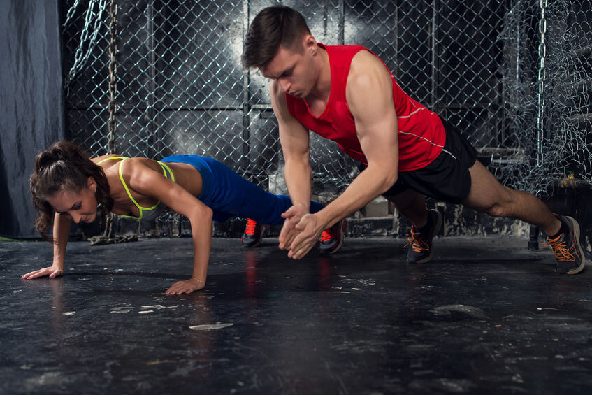 man and woman doing clapping push-ups at crossfit gym