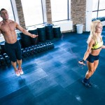 Man and woman workout with jumping rope in crossfit gym