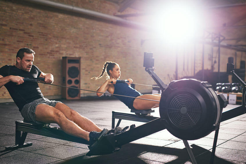 Two young sportsmen training on rowing machines