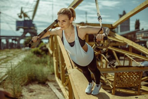 Woman doing upper body exercise using trx suspension