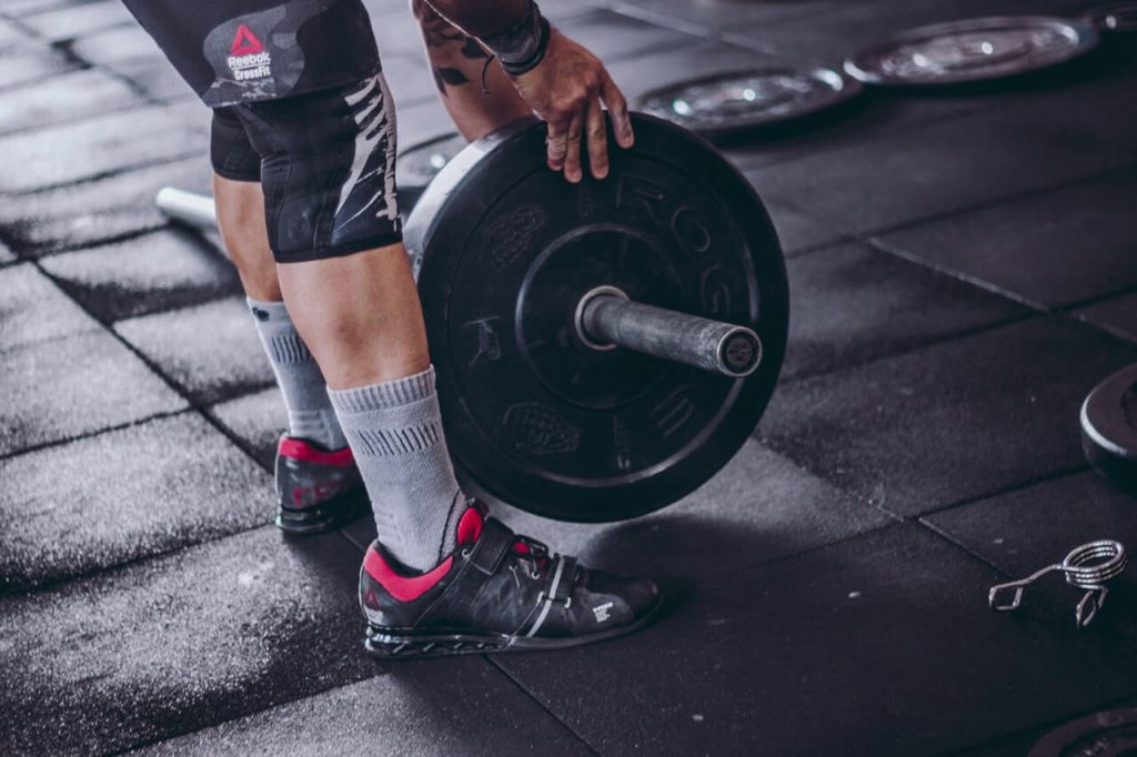 man with knee sleeves picks up barbell