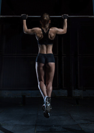 Girl doing pull-up exercise in CrossFit gym