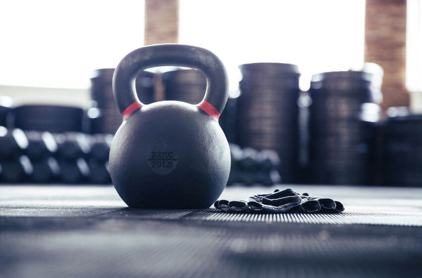 closeup image of a kettlebell and CrossFit gloves in gym