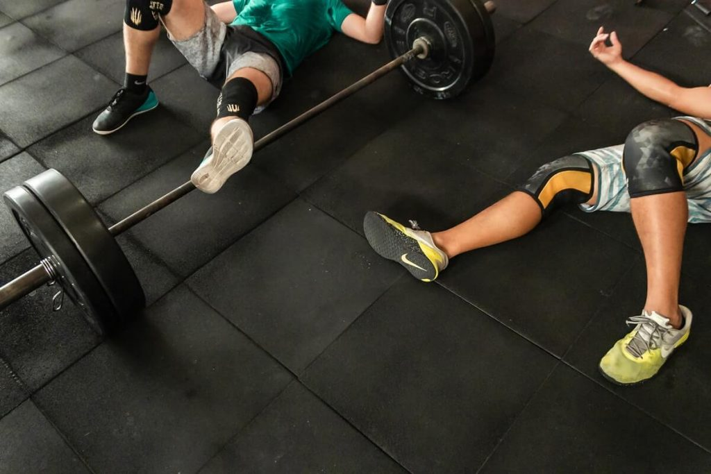 two men lying on CrossFit gym floor beside Olympic barbell