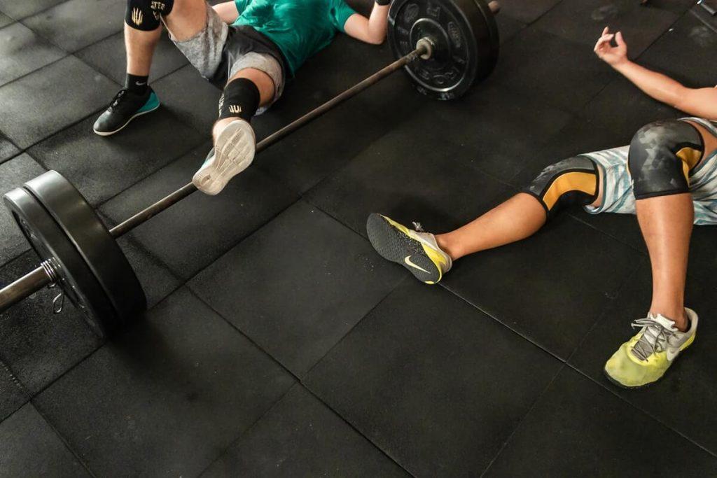 two men lying on CrossFit gym floor beside Olympic barbell