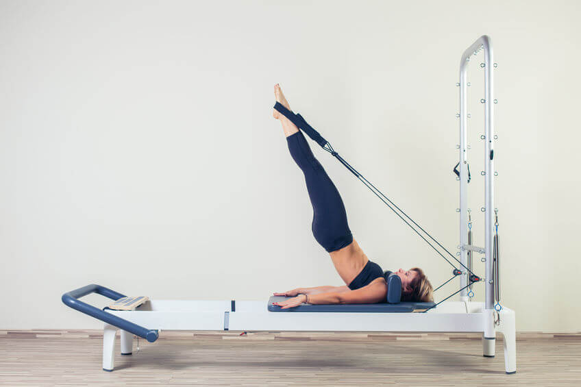 woman doing Pilates reformer workout at the gym