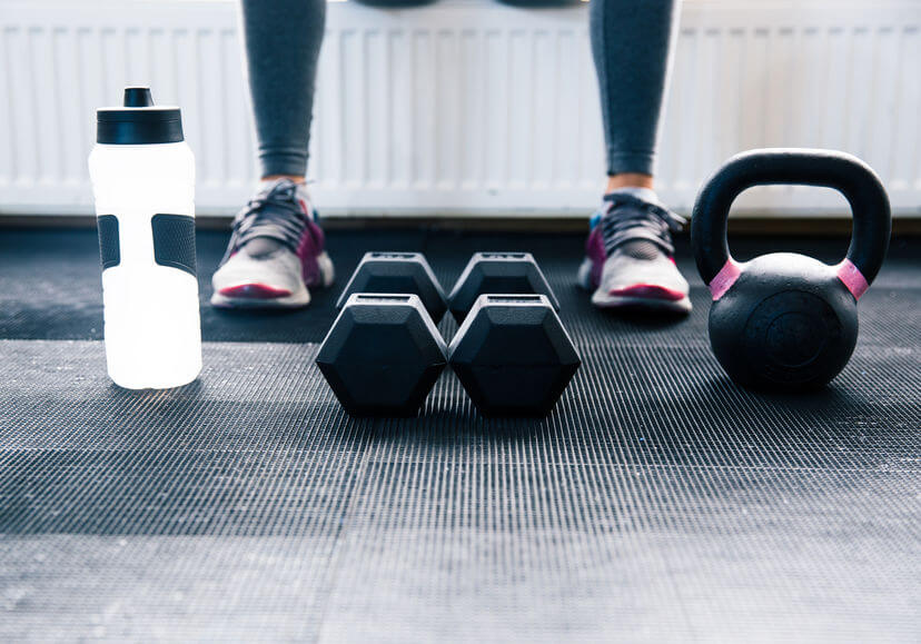 woman sitting at gym with dumbbells, protein shaker and kettlebell
