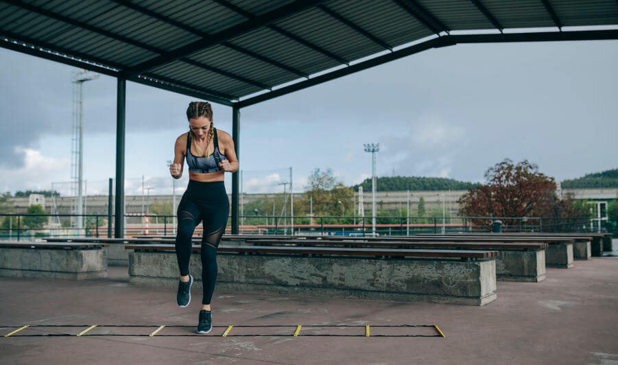 woman training jumping on an agility ladder