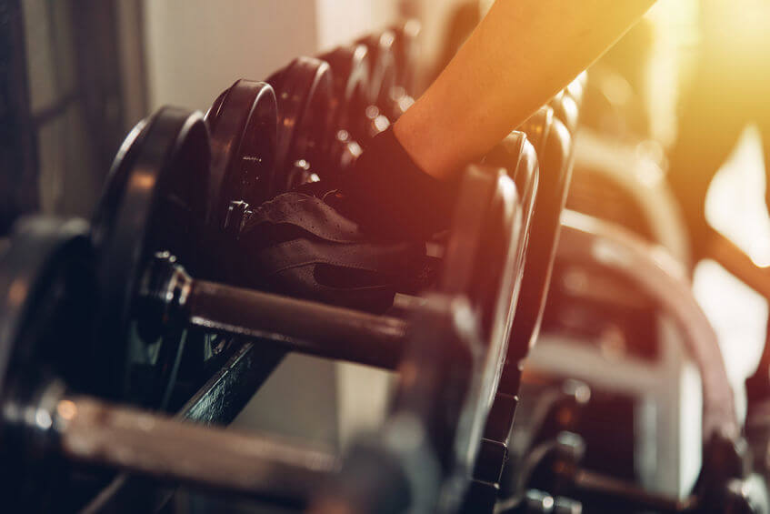 woman wearing weight lifting gloves holding dumbbell at gym