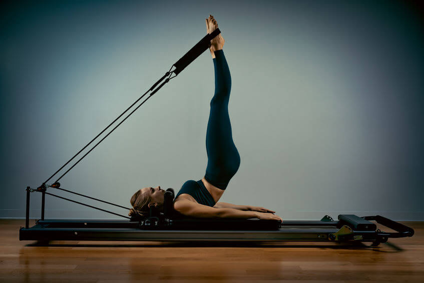 young woman doing pilates exercises with a reformer