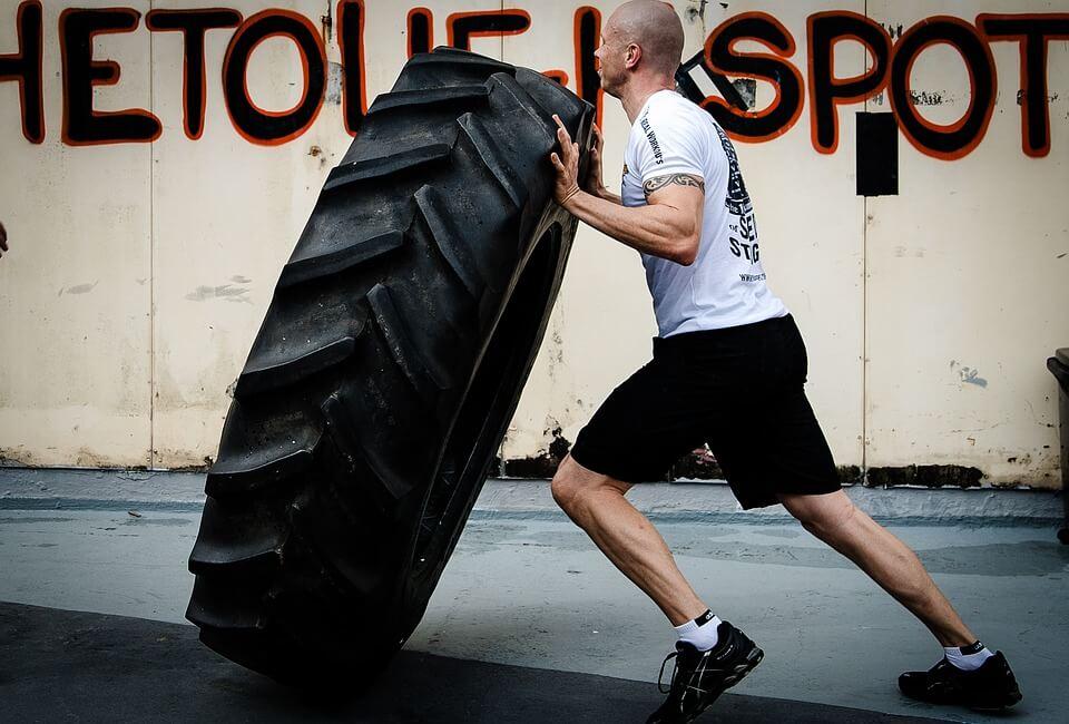 man lifting tire