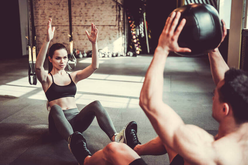 two persons working out with medicine ball in the gym