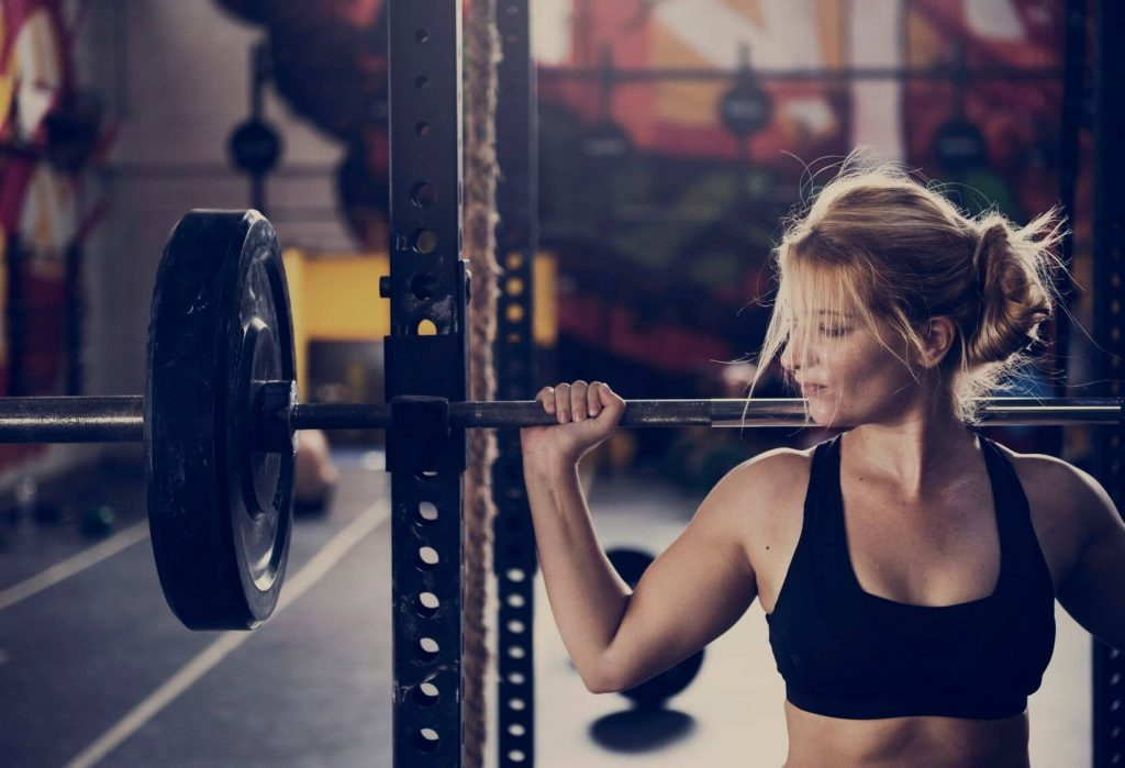 women doing squat workout with power rack