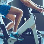 man in sportswear cycling at gym