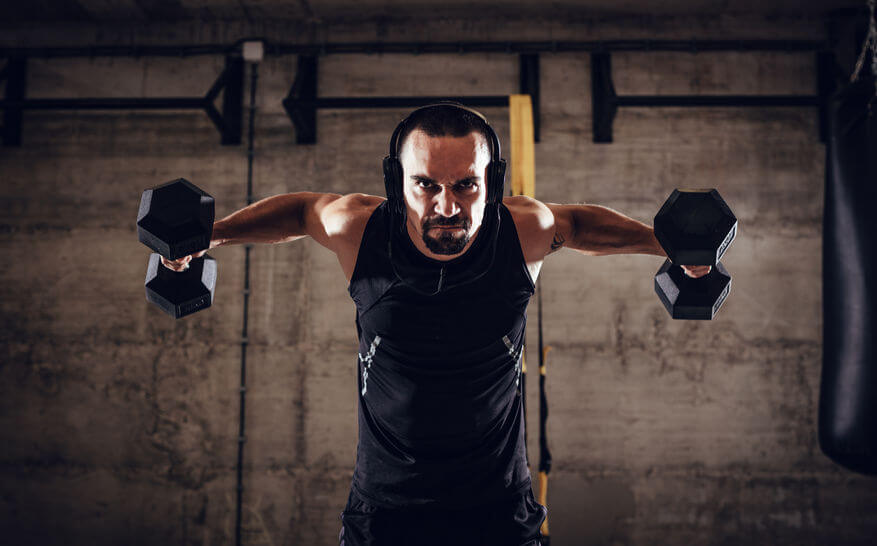 man with headphones doing exercise in CrossFit gym