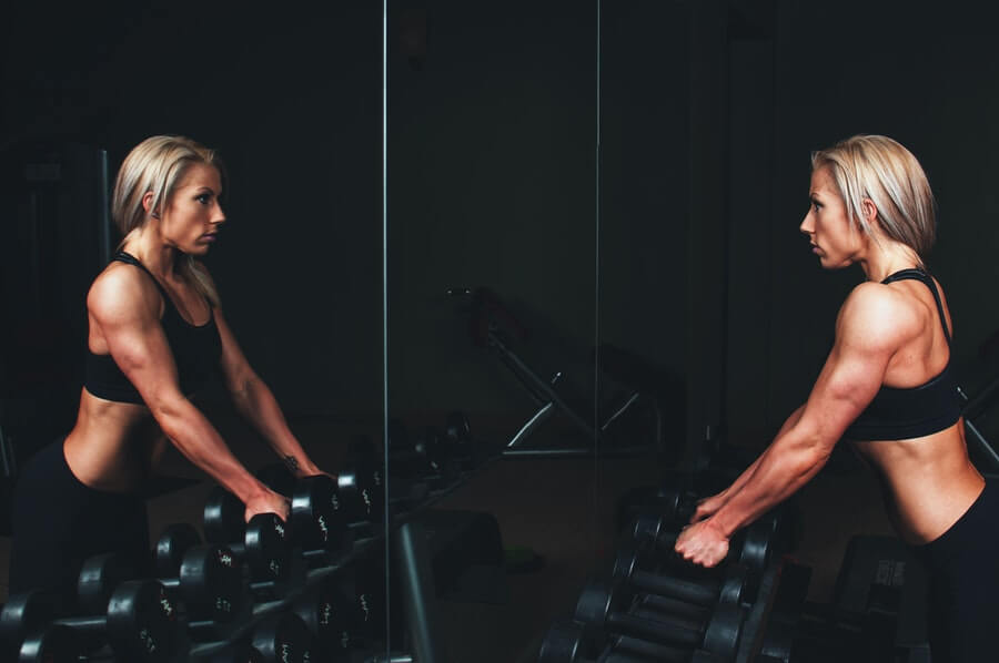 woman in the gym close to dumbbells rack