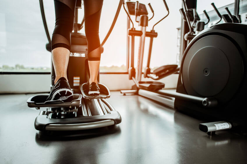 woman working out on an elliptical trainer in gym
