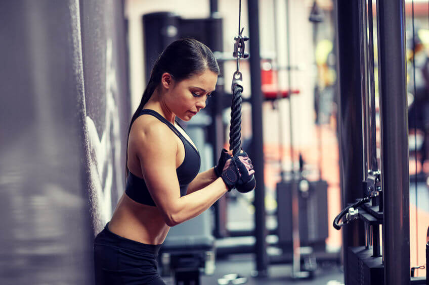woman flexing arm muscles on cable machine in home gym