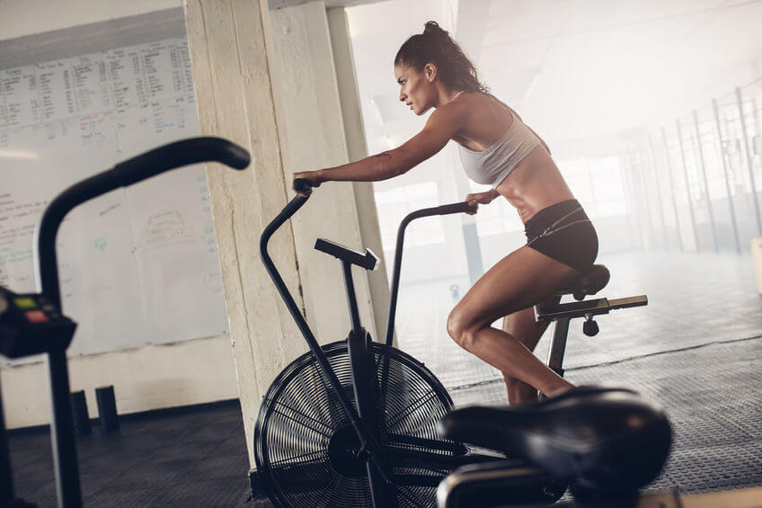 young woman using air resistance bike at the gym