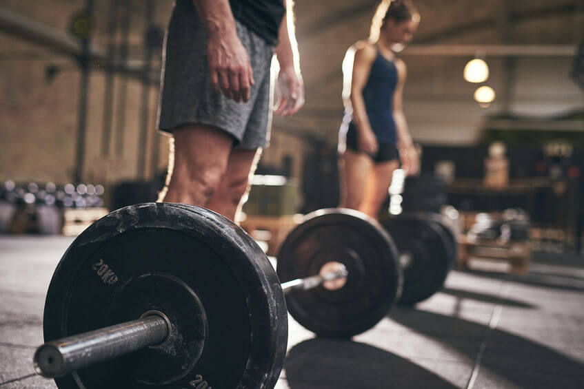 Fit people standing at barbells before exercise