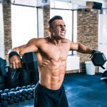 Muscular man lifting rubber hex dumbbells at gym