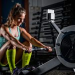 Woman athlete exercising on rowing machine at home gym