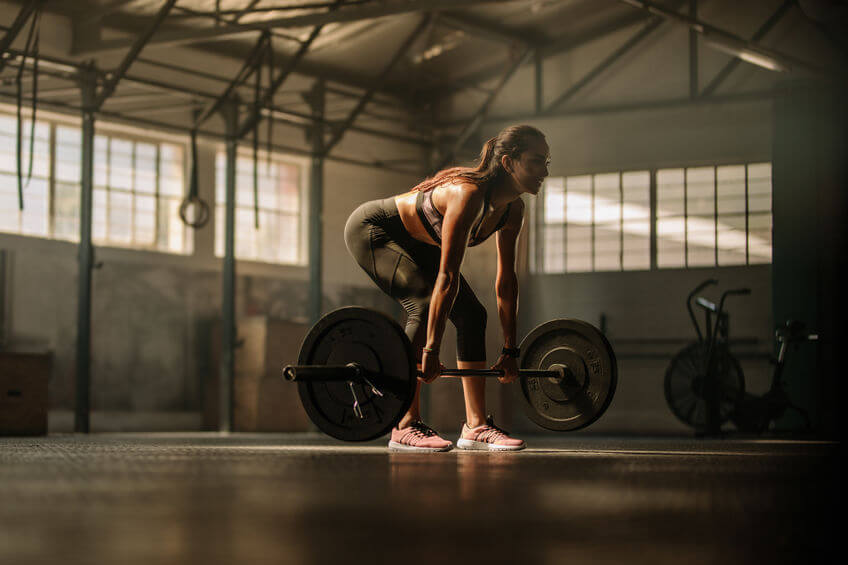 female athlete performing weight lifting exercise at gym