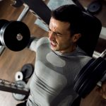 man holding dumbbells and working bench press at gym