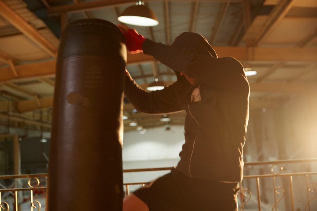 man kicking the heavy bag