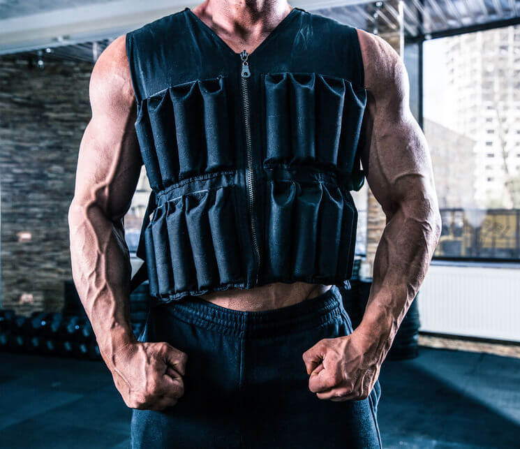man wearing in weighted vest in gym