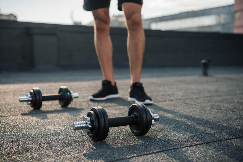 sportsman standing near adjustable dumbbells