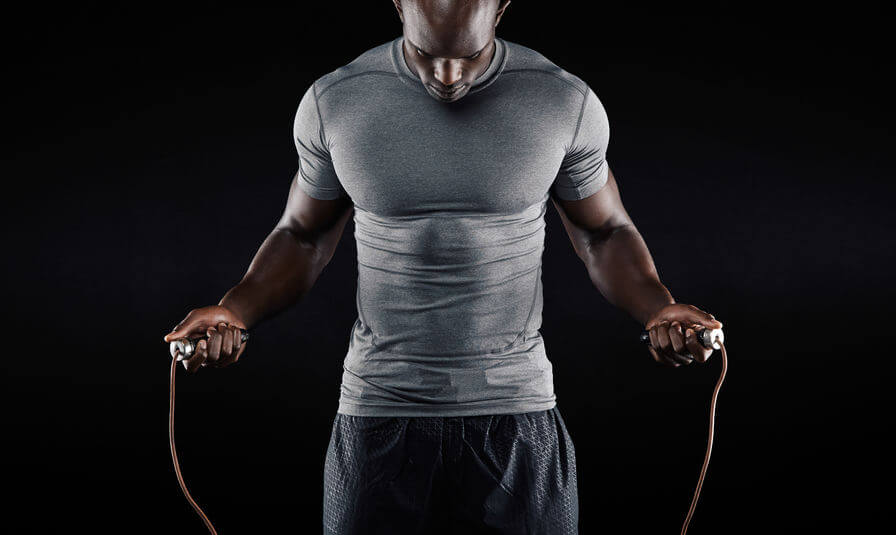 Man with compression shirt exercising with jumping rope