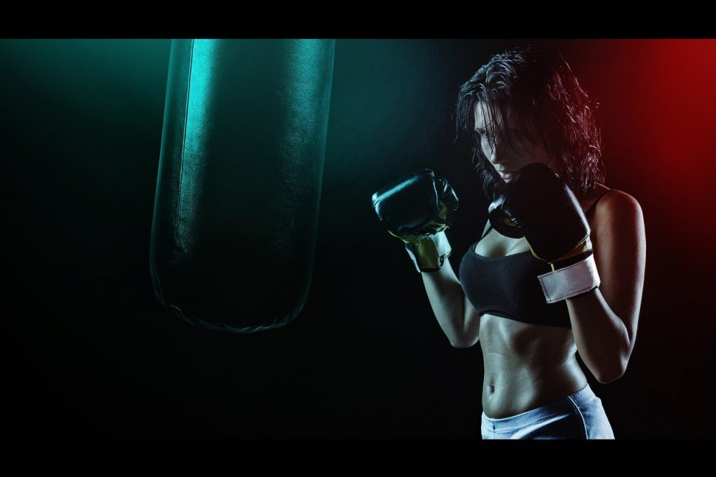 girl boxing workout with heavy bag