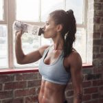 Fit young woman drinking pre workout drink in the gym