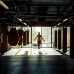 Men warming up in boxing gym with punching bags