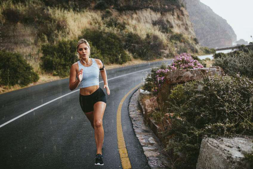 female athlete running on road during rain