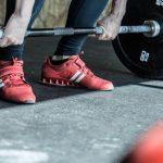 man wearing weightlifting shoes and lifting heavy barbell