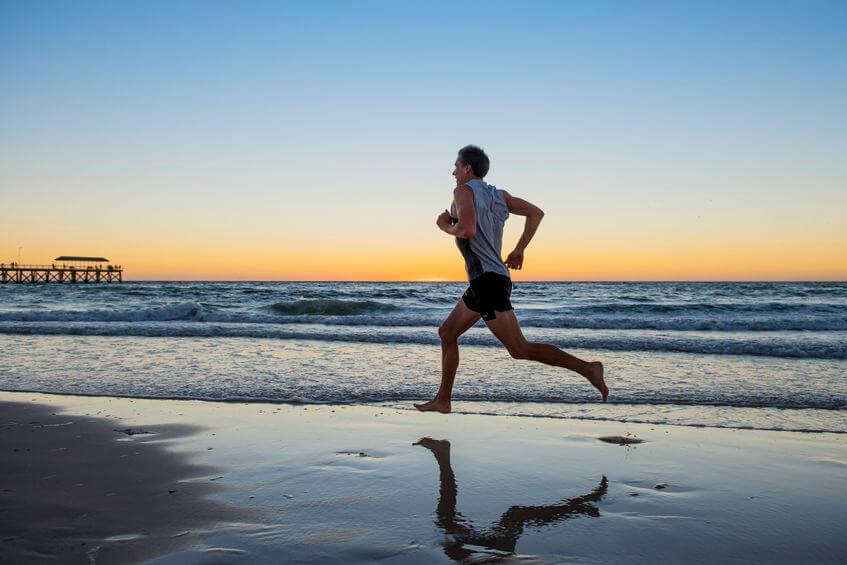 runner man training on sunset beach running barefoot