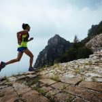 woman trail runner wearing hydration backpack and running on the mountain
