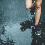 running in the rain on wet asphalt road