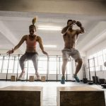 couple doing set of box jumps in crossfit gym