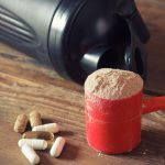 whey protein powder in scoop with nighttime fat burner vitamins