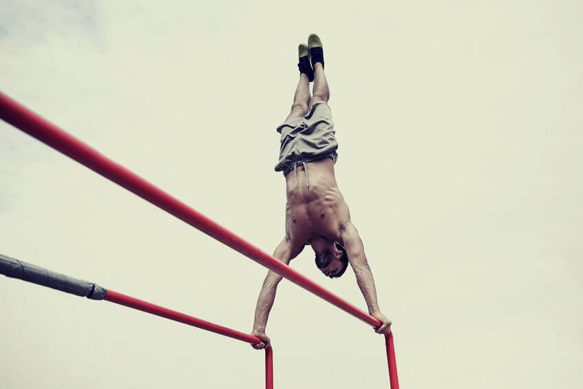 calisthenics training - man exercising on parallel bars