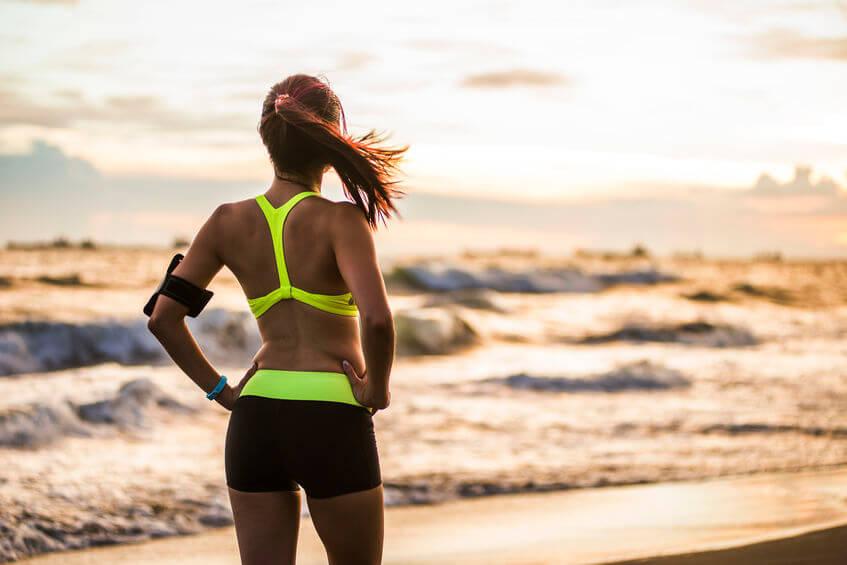 woman running at sunrise beach