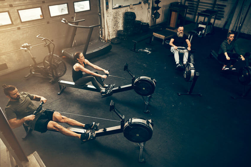 people working out on rowing machines in CrossFit gym