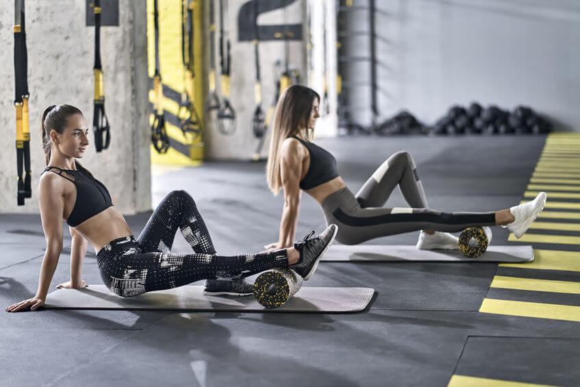 two girls training in gym with foam roller
